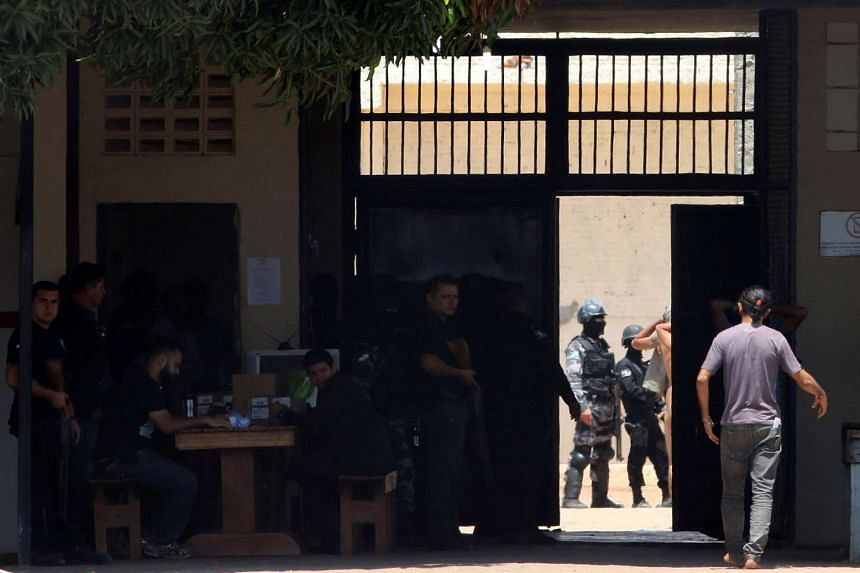 Riot police officers check inmates after clashing between rival criminal factions at a prison in Boa Vista, Brazil, on Oct 17, 2016.