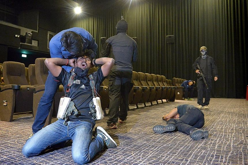 """A """"terrorist"""" strapping an explosive vest on a hostage in a cinema, as part of a media preview to an islandwide counter-terrorism exercise that started yesterday and is set to end early this morning. The exercise comes as Singapore ramps up its readi"""