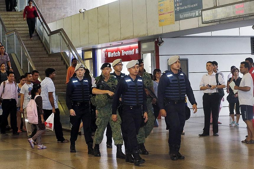 Public Transport Security Command police officers and SAF soldiers patrolling Jurong East MRT station during the evening peak hours yesterday. Security teams were deployed at various locations, including public transport hubs, shopping malls, residen