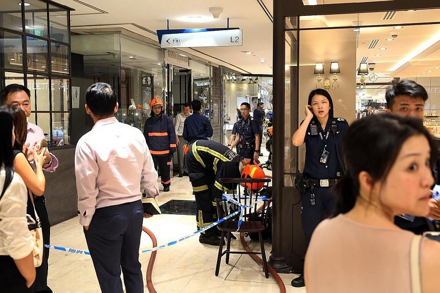 SCDF personnel and police officers outside Masterpiece Time & Jewels yesterday evening after a small fire broke out in the shop's ceiling. The police are investigating the cause of the fire.
