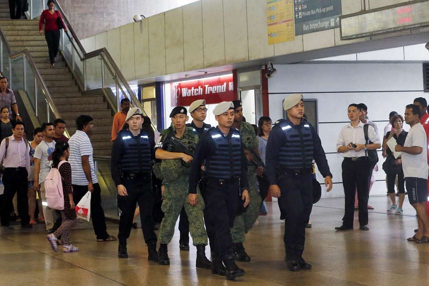 Public Transport Security Command police officers and SAF soldiers patrolling Jurong East MRT station on Oct 17, 2016.