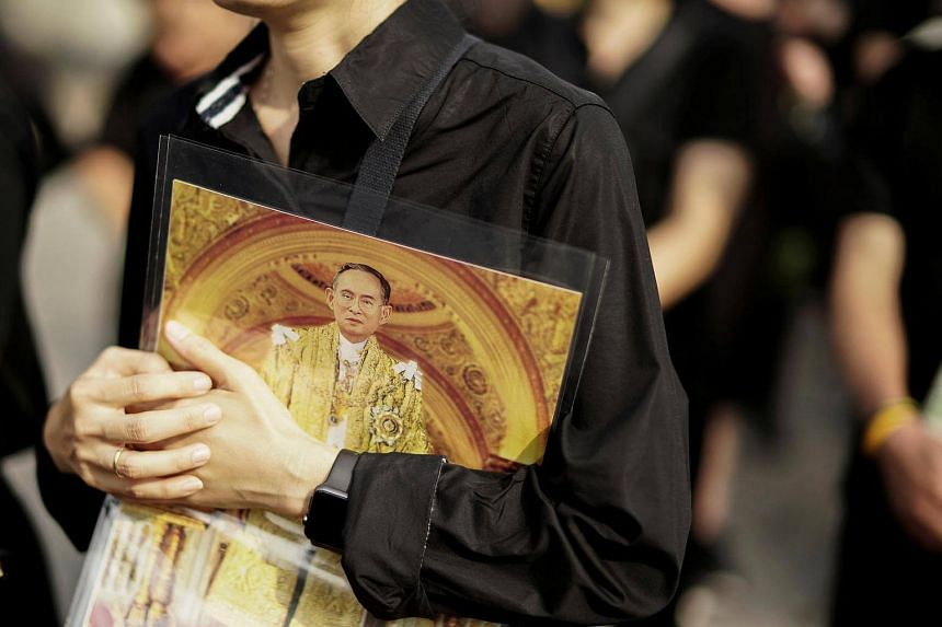 A mourner holds up a picture of Thailand's late King Bhumibol Adulyadej as she waits in line to offer condolences at the Grand Palace in Bangkok.