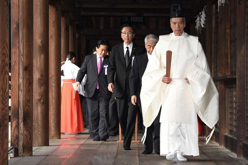 A Shinto priest (right) leads a pack of lawmakers at the Yasukuni Shrine in Tokyo on Oct 18, 2016.