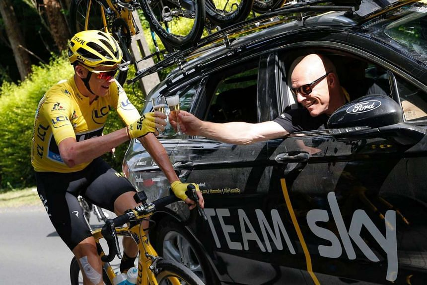 Great Britain's Christopher Froome (left), wearing the overall leader's yellow jersey, and Team Sky director Sir Dave Brailsford drink a glass of champagne at the start of the 113km twenty-first and last stage of the 103rd edition of the Tour de Fran