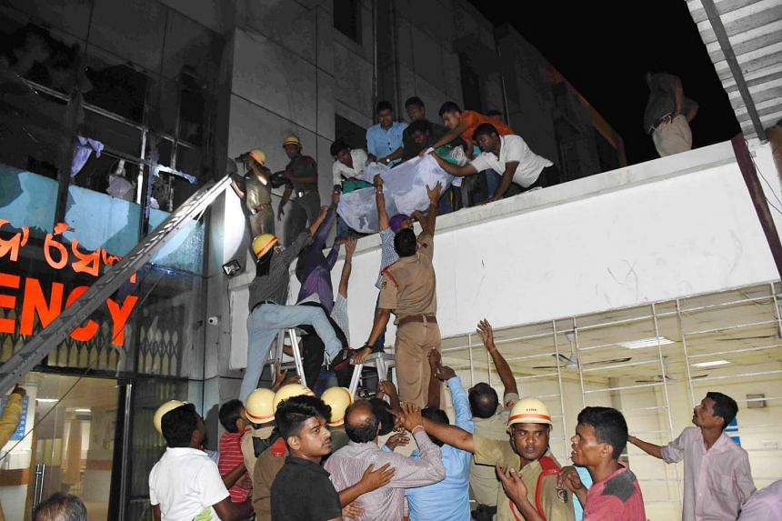 A patient is being shifted as rescue work is in progress after a fire broke out in the Intensive Care Unit (ICU) of SUM hospital in Bhubaneswar, Orissa, India, on Oct 17 2016.