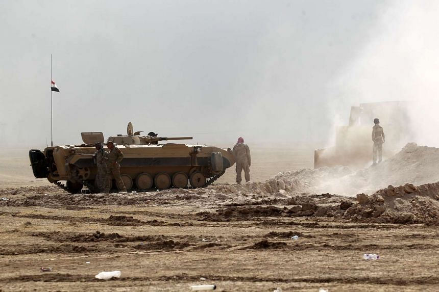 Iraqi forces hold a position in the area of al-Shurah, some 45km south of Mosul, as they advance towards the city to retake it ISIS, on Oct 17, 2016.