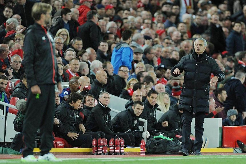 Manchester United manager Jose Mourinho (right) reacts with Liverpool manager Juergen Klopp during the English Premier League football match between Liverpool and Manchester United on Oct 17, 2016.