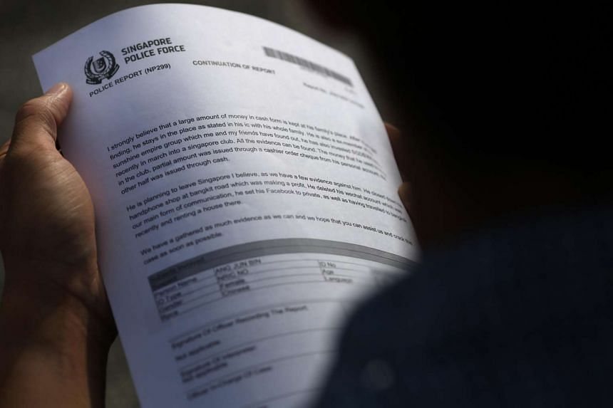 A scam victim shows his police report.