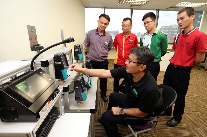 Singapore Bus Academy trainer Ho Hee Tock, 51, explaining the bus fare system to (from left) Mr Mok Kah Leong, 39, SBS trainee bus driver; Mr Yap Hong Hwi, 41, Go-Ahead bus driver; Mr Bernard Koh, 29, Tower Transit bus driver; and Mr Toh Swee Seng, 37, SM