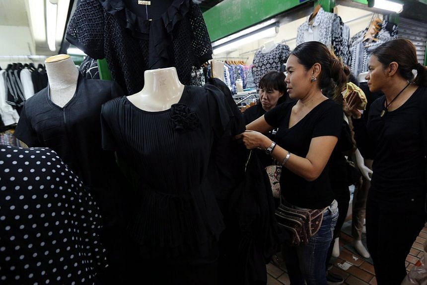 Thai people look at black shirts on sale to mourn the late Thai King Bhumibol Adulyadej on Oct 15, 2016.