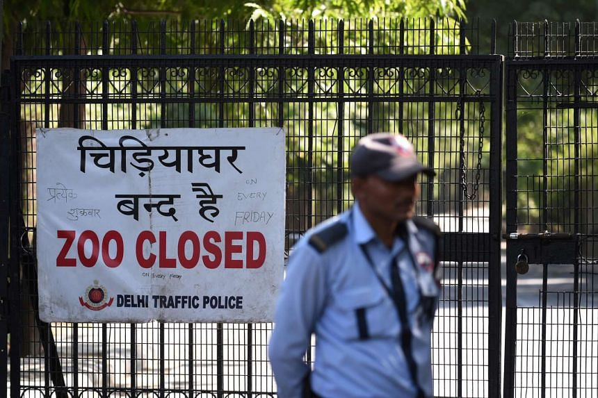 A security guard stands in front of a sign at the main gate of the Delhi Zoo, telling visitors that the zoo is closed, on Oct 19, 2016.