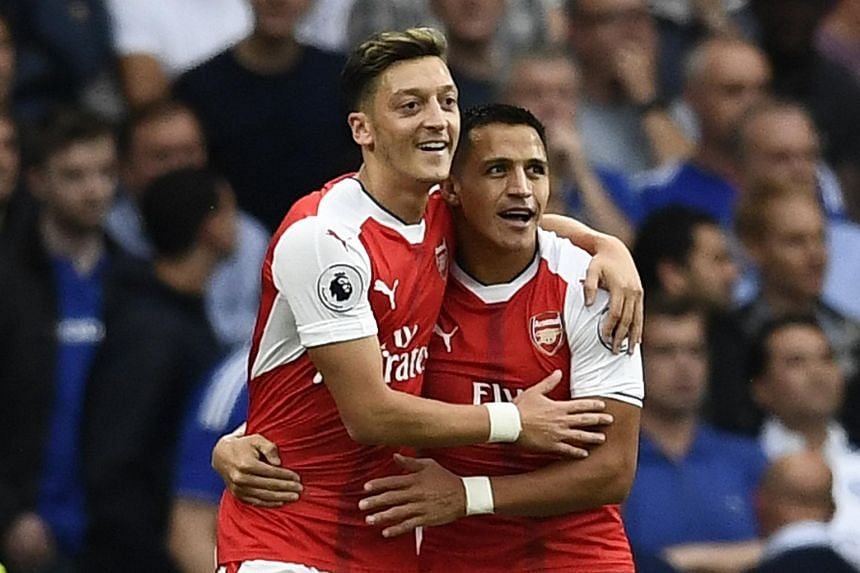 Arsenal manager Arsene Wenger is hoping that the the chase for silverware will keep Mesut Ozil (left) and Alexis Sanchez at the club.
