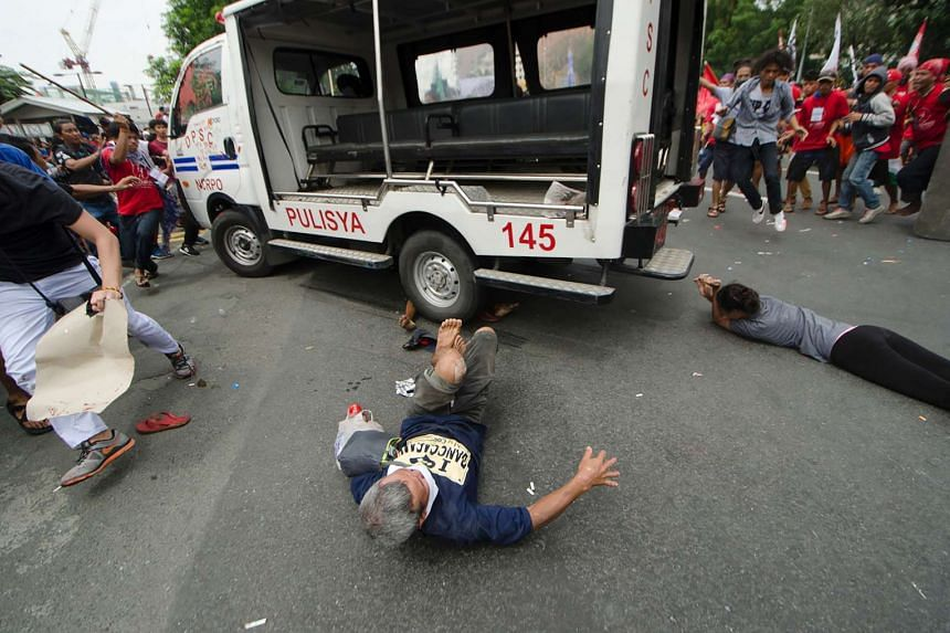 Protesters lie on the ground after being run over by a police van during a demonstrations, in Manila on Oct 19, 2016.