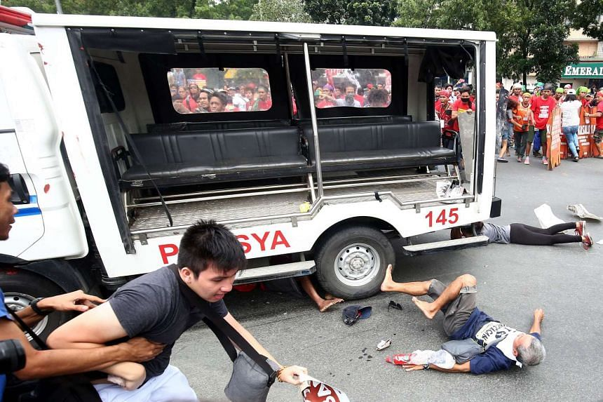 Protesters scrambling to get away from a police van after it crashed into the crowd, in Manila on Oct 19, 2016.