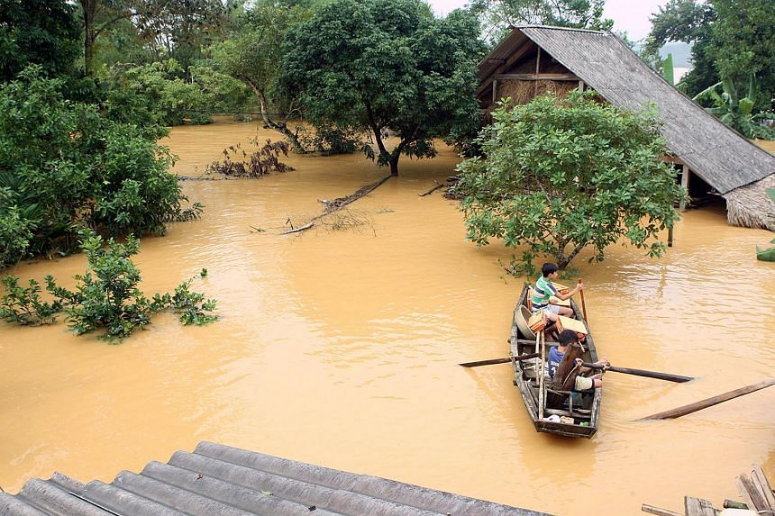 Villagers in a boat transporting boxes of instant noodles past flooded homes in a village in Vietnam's Huong Khe district on Oct 16, 2016.
