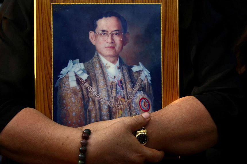 A mourner holds a portrait of the late Thai King Bhumibol Adulyadej in Bangkok on Oct 14, 2016.