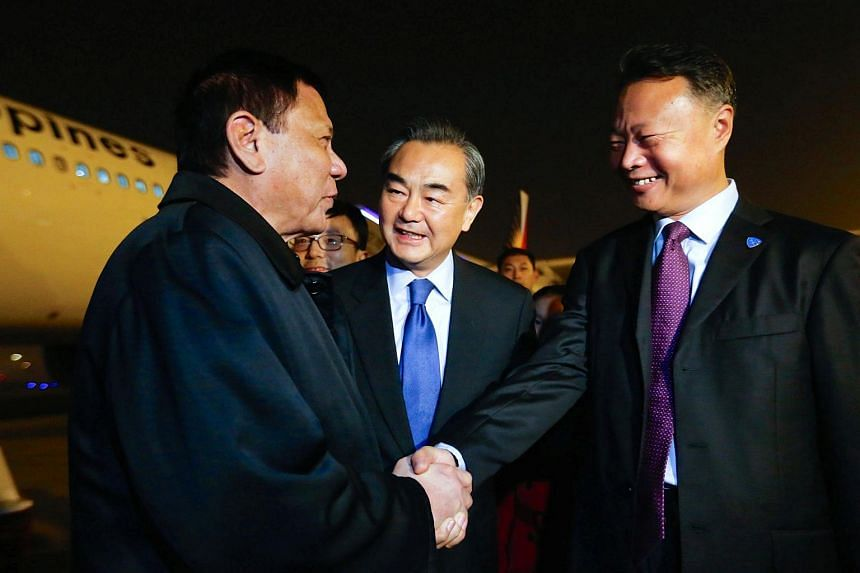 Chinese Foreign Minister Wang Yi (centre) looks on as Philippine President Rodrigo Duterte (left) shakes hands with Chinese ambassador to the Philippines Zhao Jianhua (right) in Beijing on Oct 18, 2016.