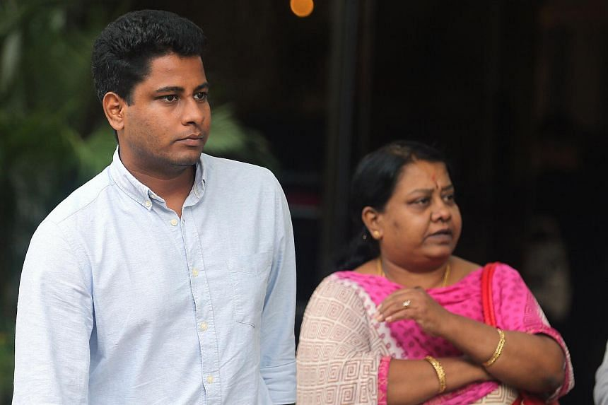 Vandana Kumar Chidambaram (left), who pleaded guilty to one charge of failing to report for NS for three years, six months and two days, leaves the State Courts with his mother Madam Sunthravalli Chelliah on Oct 18, 2016.