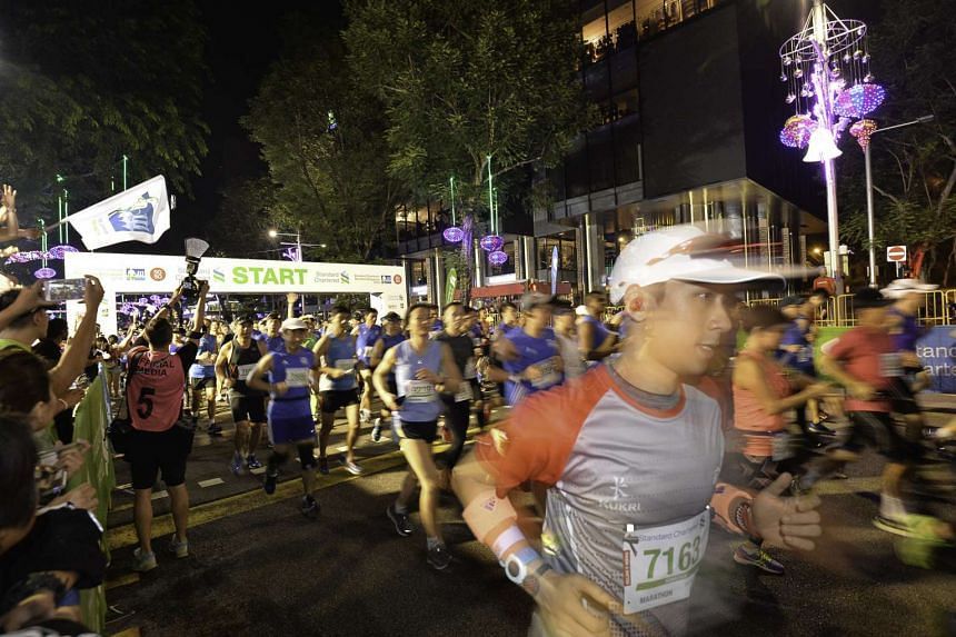 Participants of the Standard Chartered Marathon Singapore take off at the starting point on Dec 6, 2015.