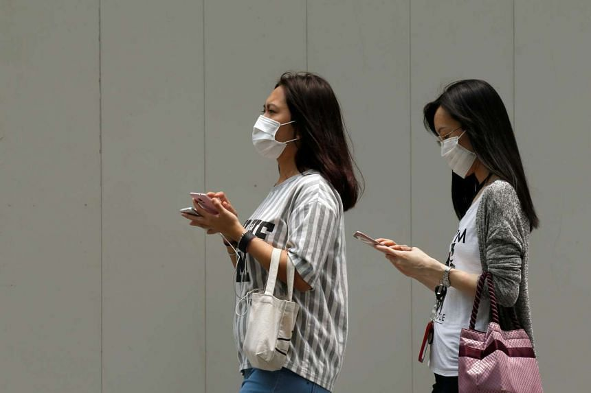 Women wearing face masks use their mobile phones as haze shrouds Singapore's central business district on Aug 26, 2016.
