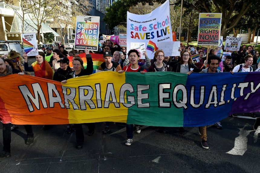 A file photo taken on June 25, 2016, shows pro-gay marriage supporters carrying a rainbow banner and flags during a rally in Sydney.