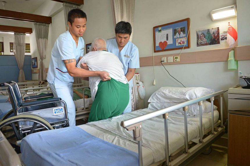 Male nurses Grenel A. Libed (right) and Aung Tin Oo (left) transferring an elderly resident to a bed at the Bethany Methodist Nursing Home.