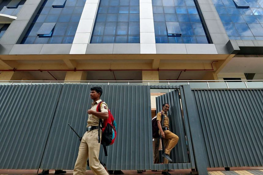 Policemen walk out of a call centre in Mira-Bhayander, on the outskirts of Mumbai.