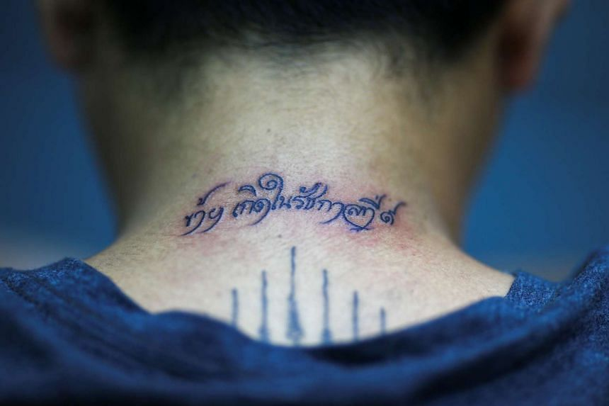 "Mr Piyaphan Phanwiroj shows a newly-inked tattoo that reads ""I was born in the reign of King Rama IX"" on the back of his neck at a tattoo shop in Bangkok on Oct 18, 2016."