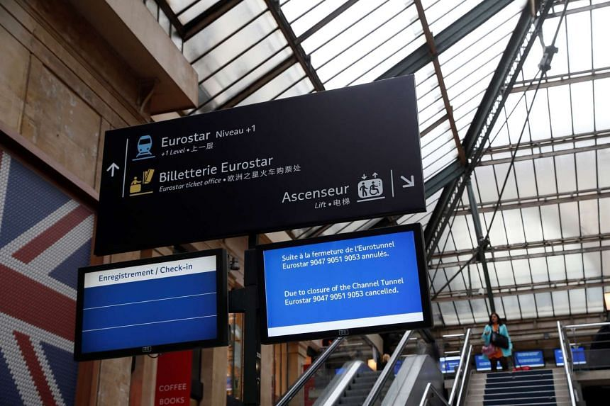 Passengers look at an information board as they wait for a train at the Gare du Nord railway station in Paris on Oct 18, 2016, after traffic through the Channel tunnel between France and Britain was stopped in both directions due to a power problem.