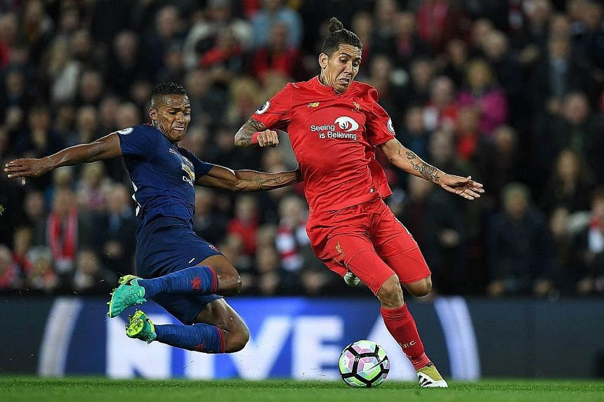 United's Antonio Valencia about to get in a crunching tackle on Liverpool's Roberto Firmino. The Reds enjoyed the lion's share of play on Monday but lacked patience.
