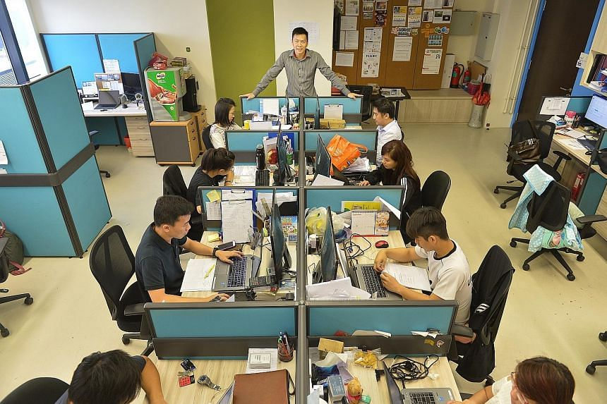Mr Teo (centre) with his staff in their office. He says that from the start, Elitez's proposition was that it would not be the cheapest agency in the market but would focus a lot on client satisfaction and value creation.