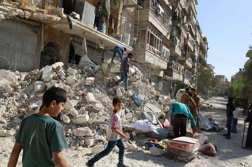 People remove belongings after an air strike in the rebel-held besieged al-Qaterji neighbourhood of Aleppo, Syria, Oct 17, 2016.
