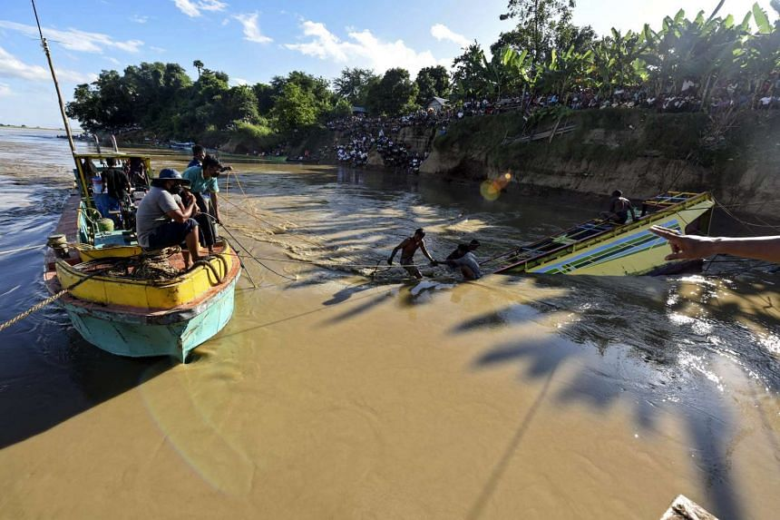 Local rescue workers try to pull a sunk ferry boat from the Chindwin river near the city of Monywa, Myanmar.