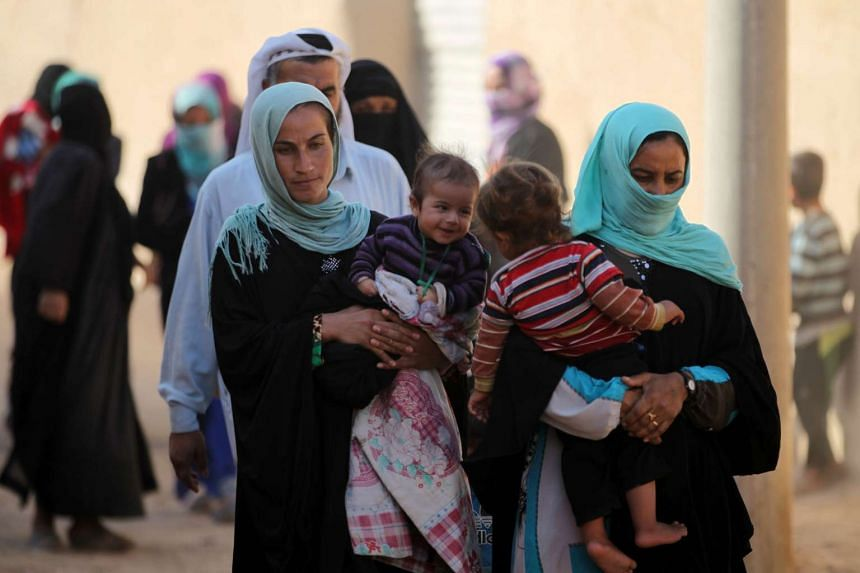 Displaced Iraqis from Bajwaniyah village, about 30kms south of Mosul, approach security forces on Oct 18, 2016, after they liberated the village from ISIS militants.
