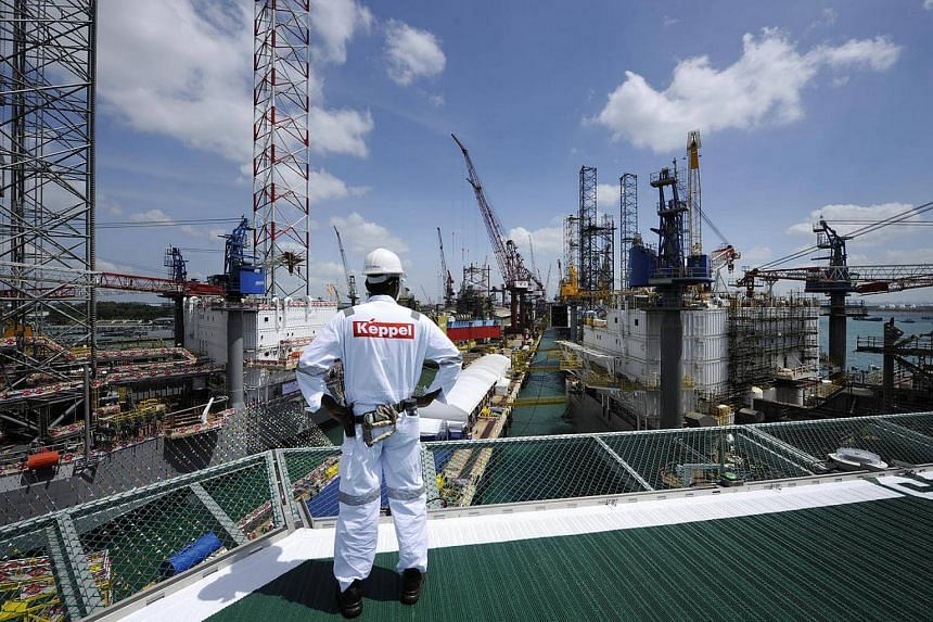 A Keppel Corp employee looks at jack-up rigs (right) under construction at the Keppel FELS shipyard in Singapore.
