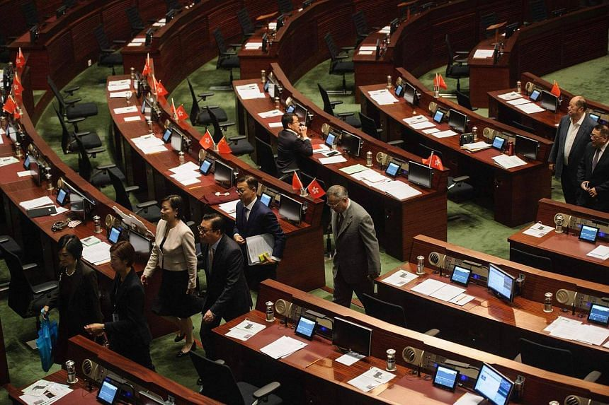 Pro-Beijing legislators walk out of the main chambers in protest against the second swearing-in of pro-independence lawmakers at the Legislative Council in Hong Kong.