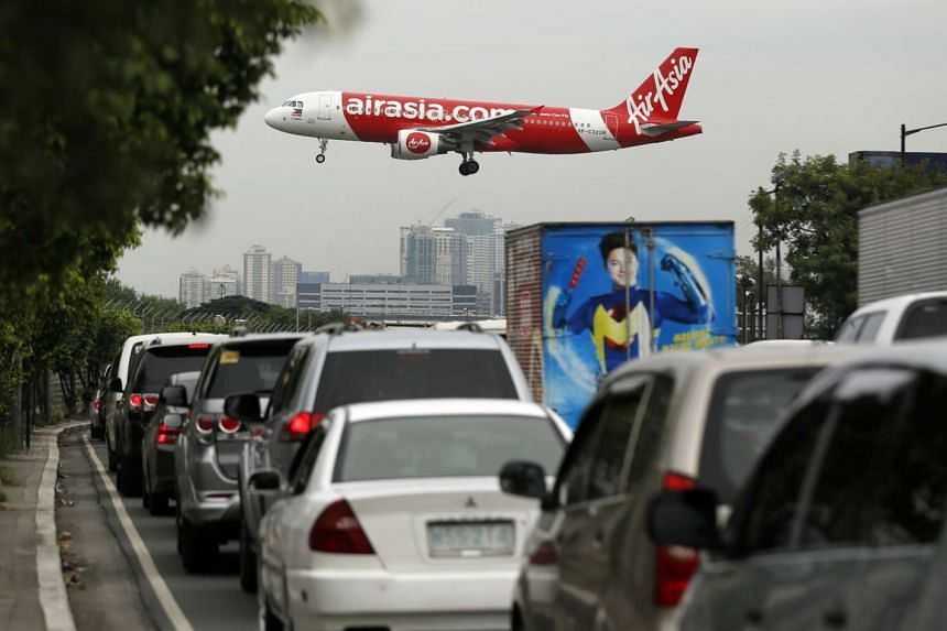 An AirAsia Airline airplane flies over cars as it lands at Manila's international airport, Philippines on Oct 19, 2016.