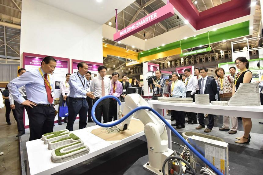 Mr Wong, the National Development Minister (third from left) and BCA's Dr Keung (fourth from left) with NTU's 3D printer, which can produce concrete structures.