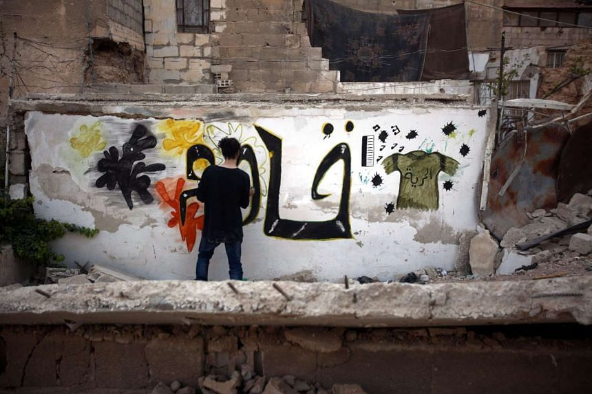 """Syrian graffiti artist Noor creating graffiti that reads """"Fight, Resist"""" on a destroyed wall in a rebel-held neighbourhood on the outskirts of Damascus in Syria on Sunday. More than 250,000 people are under government siege in the city of Aleppo, once Syr"""