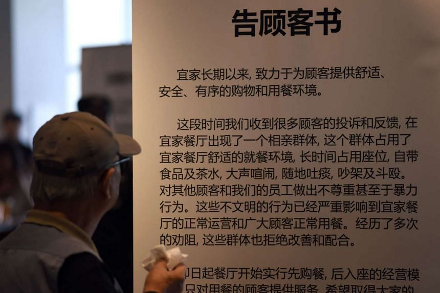 """A man looking at a notice in Ikea Shanghai's restaurant. Its """"no food, no seat"""" rule is to deter a group of older people looking for love from occupying its tables and socialising for many hours over free coffee."""