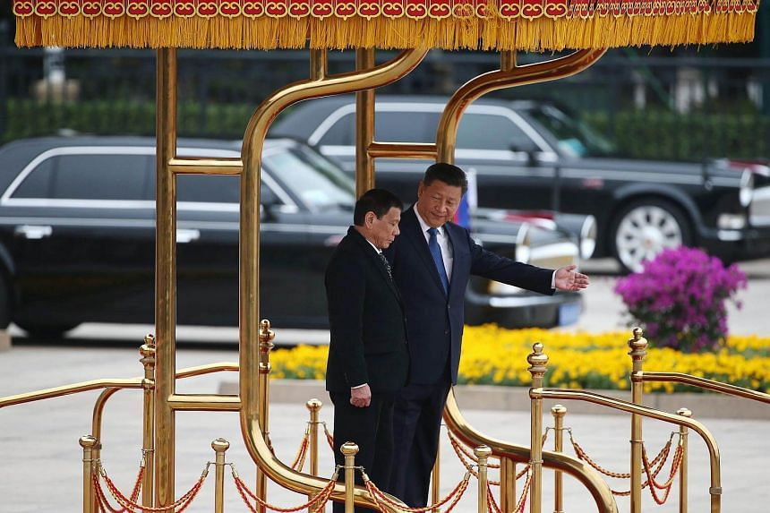 Chinese President Xi Jinping gestures to Philippines President Rodrigo Duterte as they review honour guards during a welcome ceremony at the Great Hall of the People in Beijing, China on Oct 20, 2016.