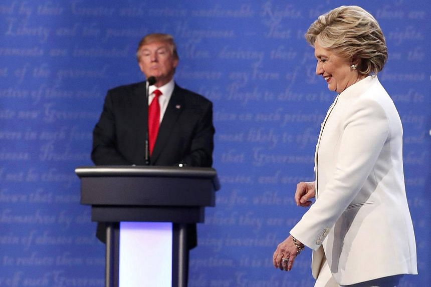 Hillary Clinton walks off the debate stage as Donald Trump remains at his podium after the conclusion of their third and final 2016 presidential campaign debate