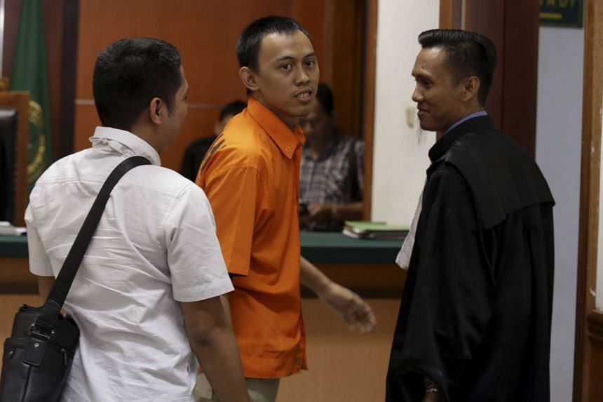 Dodi Suridi (centre) standing near his lawyer during his trial in Jakarta on Oct 20, 2016.