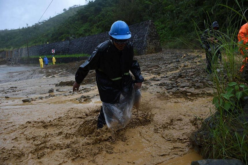 Workers cross a destroyed road caused by a landslide brought about by typhoon Haima in Karanglan town, north of Manila on Oct 20, 2016.