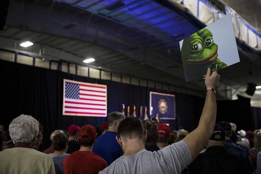 An attendee holds up a sign of Pepe the Frog, a cartoon tied to anti-Semitism and racism that has become an unofficial mascot of the alt-right, during a campaign event with Donald Trump at a sports complex in Bedford, NH.