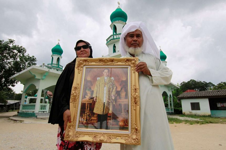 Hayim Mohammed Tolema (right) and a woman pose with a portrait of late King Bhumibol Adulyadej outside a mosque in Yala, Thailand on Oct 20, 2016.