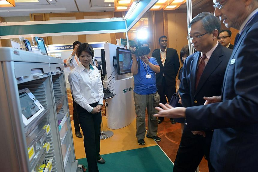 Minister for Health Gan Kim Yong views ST Healthcare's SmarT Solution for hospital logistics with ST Healthcare CEO Dr. Richard Tan (extreme right) at the National Seminar on Productivity in Healthcare.