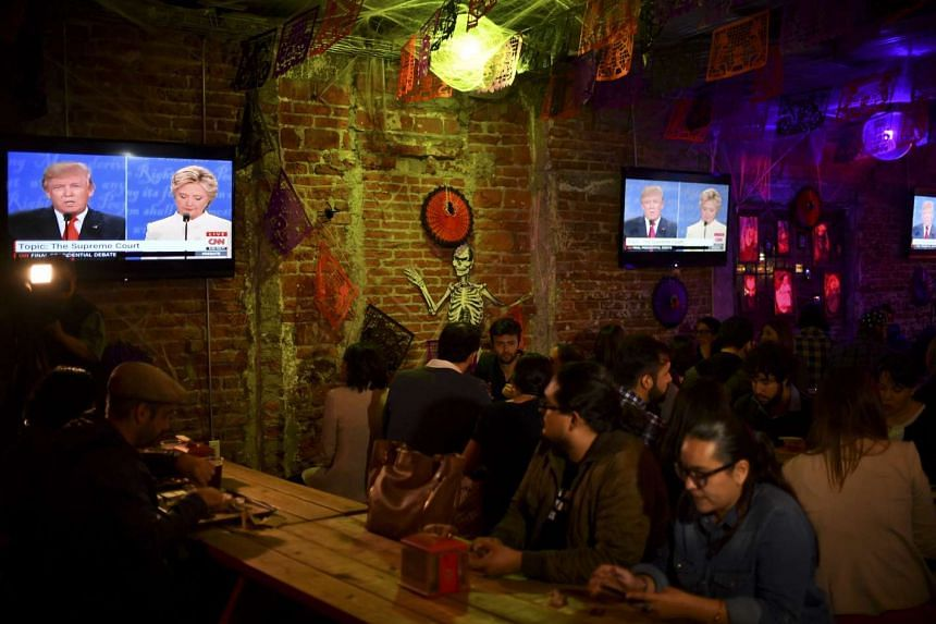 Locals and Americans watching the US presidential debate in a bar-restaurant in Mexico City, on Oct 19, 2016.
