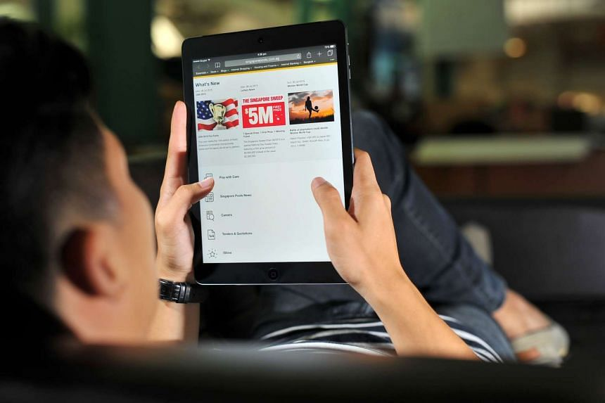 A man looking at Singapore Pools website on a tablet.