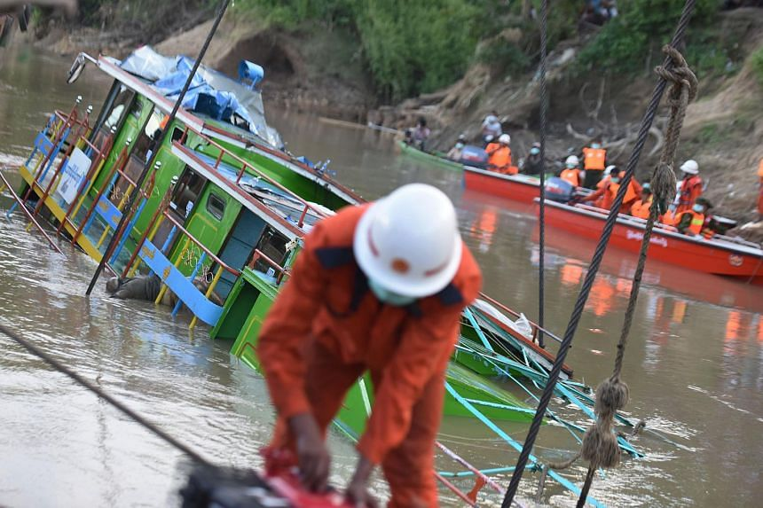 Rescue personnel from the Myanmar Fire Services Department refloat a ferry which sank in the Chindwin River in the Sagaing region on Oct 19, 2016.